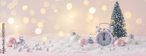 Fotografía  Pink and White glass Christmas balls with an alarm clock on a snowflake and ligh