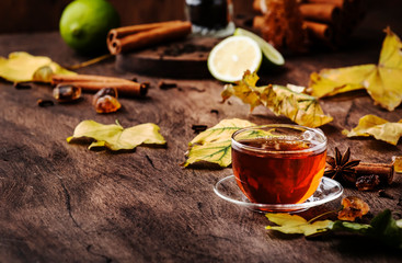Autumn hot black tea in glass cup, old wooden table background, selective focus