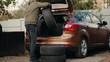 A man loads winter tires in a car trunk. Motorist prepares changes car tires from summer to winter