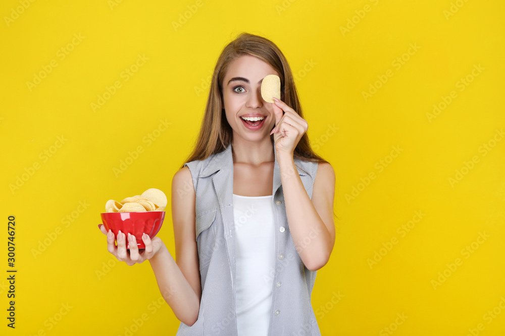 Fototapeta Young beautiful girl with potato chips in bowl on yellow background