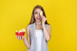 Young beautiful girl with potato chips in bowl on yellow background