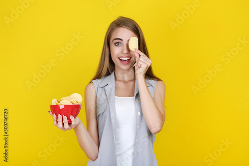 Fotomural Young beautiful girl with potato chips in bowl on yellow background