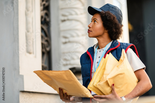 Cuadros en Lienzo  African American postal worker delivering mail in the city.