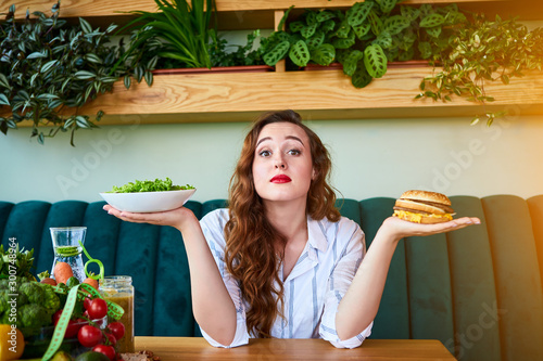 Fotomural  Beautiful young woman decides eating hamburger or fresh salad in kitchen
