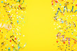 canvas print picture - Colorful ribbons with paper stars and confetti on yellow background