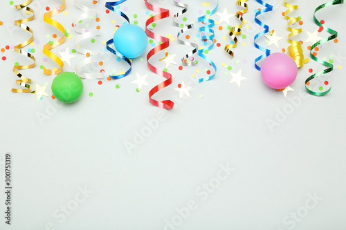 Photo  Colorful ribbons with rubber ballons and confetti on grey background