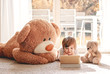 canvas print picture - Cute little child watching cartoons on digital tablet device lying on floor with two soft teddy bear toys at home. Modern childhood.