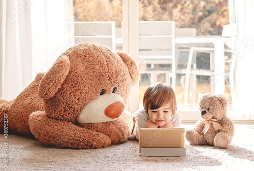 Fototapeta Cute little child watching cartoons on digital tablet device lying on floor with two soft teddy bear toys at home