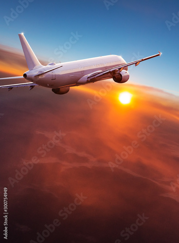 Commercial airplane flying above dramatic clouds during sunset. Fototapete