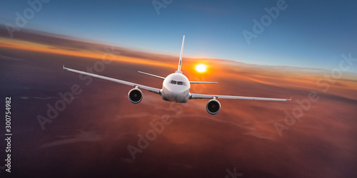 Türaufkleber Flugzeug Commercial airplane flying above dramatic clouds during sunset.