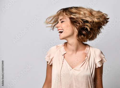 young woman in a beige short-sleeved satin blouse shakes her head with her hair Fototapeta