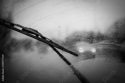 Carta da parati car windshield wipers in rainy season, black and white photo with vignetting, fr