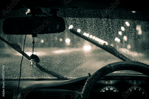 Fototapeta car windshield wipers in rainy season, black and white photo with vignetting, front and rear background blurred with bokeh effect obraz na płótnie