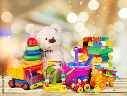 Cuadros en Lienzo Bear and colorful toys on a wooden desk on abstract light background