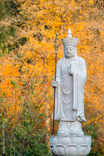 Ksitigarbha Buddha, a Bodhisattva, statue with yellow fall colors in the background