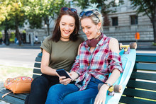 Portrait Of Smiling Young Women Sitting On Bench With Skateboard Looking At Mobile Phone