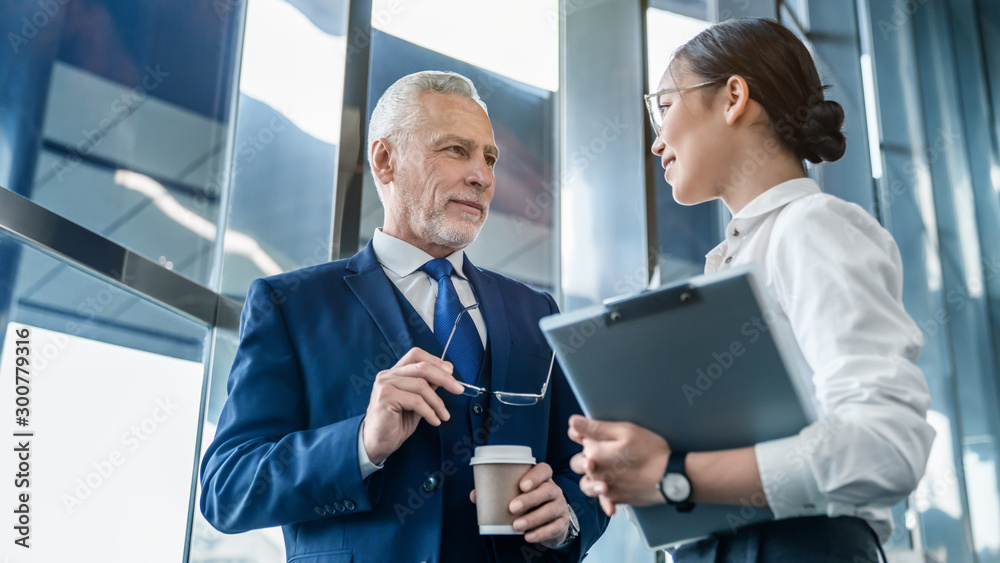 Fototapeta Business colleagues discuss business documents standing indoors