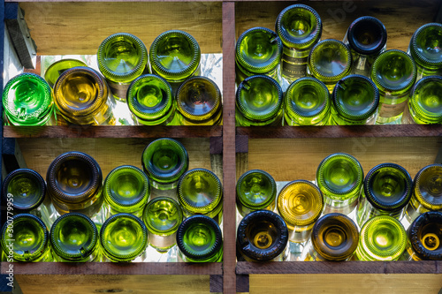 Fotomural  Wall decorated with empty wine bottles with morning light