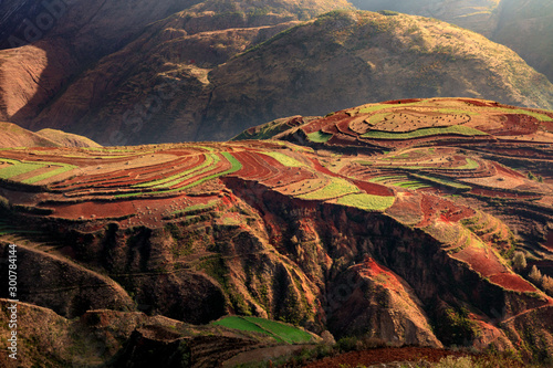 Dongchuan Red Earth Multi-Colored Terraces - Red Soil, Green Grass, Layered Terraces in Yunnan Province, China. Chinese Countryside, Agriculture, Exotic Unique Landscape. Farmland, Agriculture