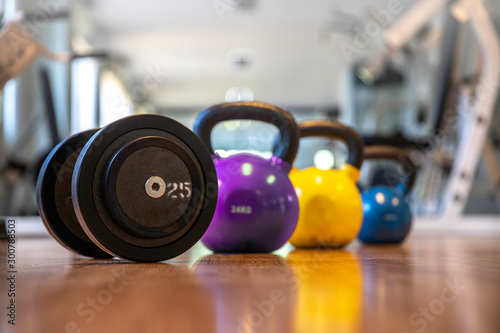 Poster Fitness Hand weights Fitness exercise equipment dumbbell and blurred kettlebells weights on wood floor in gym