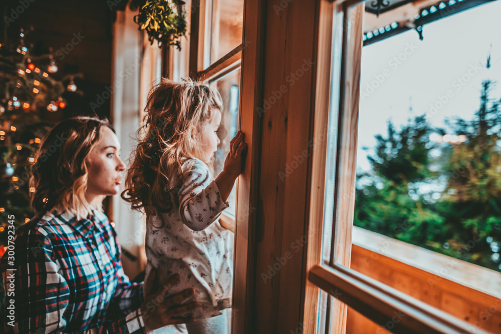 Fototapety, obrazy: Mother and Daughter Having Fun on Christmas Morning. Precious family moment, young mom playing with her toddler daughter by decorated Christmas Tree and the window, winter landscape.