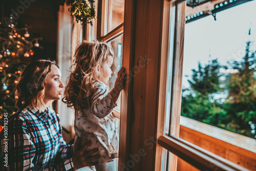 Foto auf AluDibond Grau Verkehrs Mother and Daughter Having Fun on Christmas Morning. Precious family moment, young mom playing with her toddler daughter by decorated Christmas Tree and the window, winter landscape.