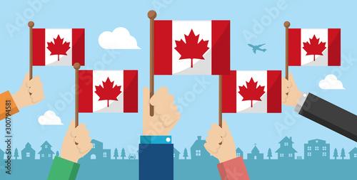 Fotografie, Obraz People holding the national flag in hand , vector banner illustration / Canada