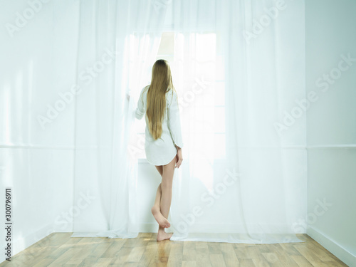 Fotobehang womenART Young beautiful blonde in front of window