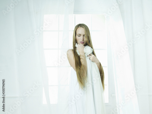 Foto auf Gartenposter womenART Young beautiful blonde in front of window