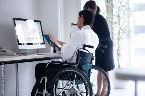 Fotografie, Tablou 仕事の打ち合わせをする車椅子の社員と女性