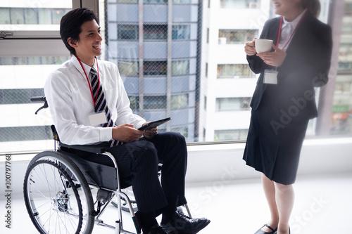Fotografie, Obraz  女性社員と談笑する車椅子のビジネスマン
