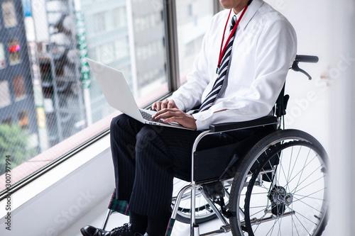Valokuva  パソコン作業をする車椅子のビジネスマン