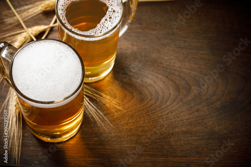 Fotomural  Glasses of Light Beer with wheat on the wooden table, copy space for your text
