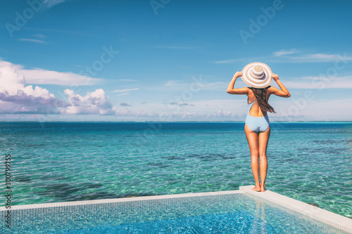 Beach vacation woman standing on infinity pool looking at blue turquoise ocean landscape with had and stripes bathing suit, vintage feel.