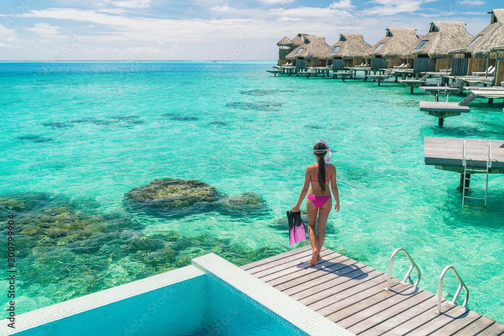 Fototapeta Luxury overwater bungalows Tahiti resort woman going snorkeling from private hotel room on Bora Bora island, French Polynesia. Travel vacation recreational activity watersport fun leisure.