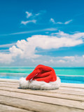 Christmas winter holidays santa hat near swimming pool of Caribbean resort travel vacation destination. Vertical backdrop of paradise vacations.