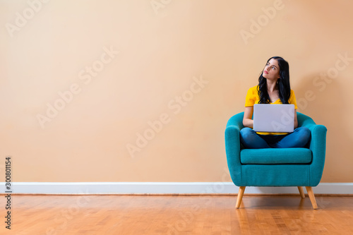 Young woman with a laptop computer in a thoughtful pose sitting in a chair