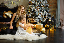 Little Girl With Her Mother Near Fir-tree In Black And Gold Holiday Interior. Christmas Celebration. Child Girl Weared In White Dress Opening A Gift Box With Fairy Light In Her Hands. New Year Eve