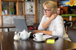 A woman with a laptop works in a cafe, she watches social networks.