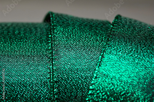 Abstract texture background of macro defocused bright shimmering green fabric holiday wrapping ribbon