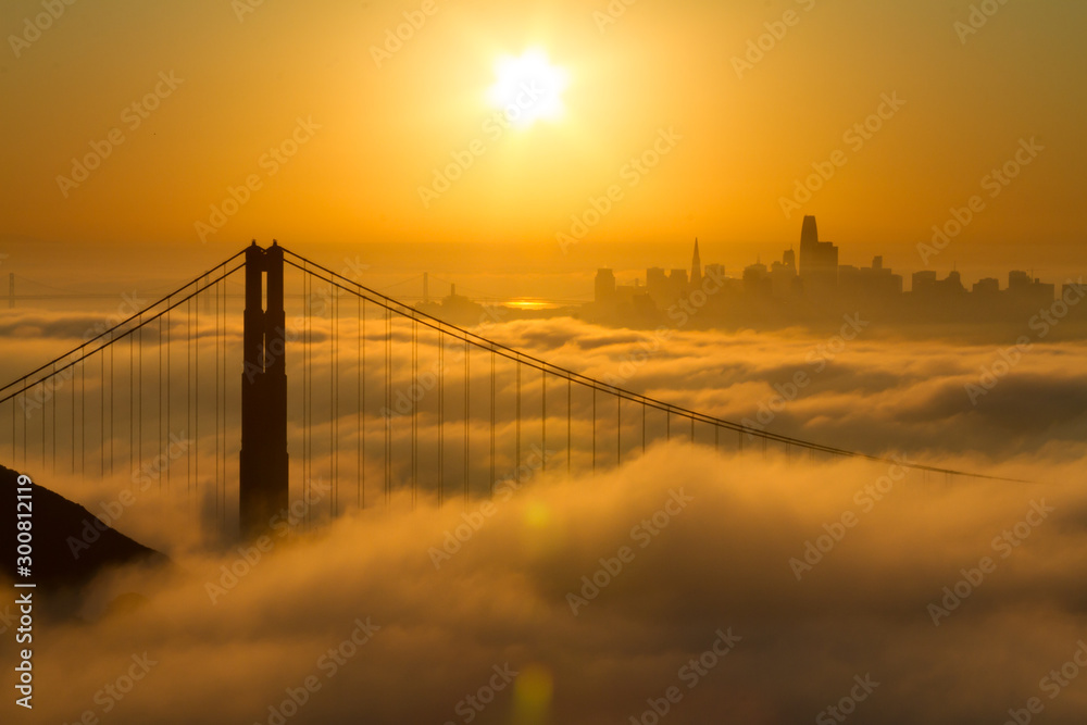 Spectacular Golden Gate Bridge sunrise with low fog and city view