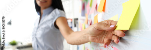 Obraz Smiling female clerk touching yellow paper sticker at whiteboard - fototapety do salonu