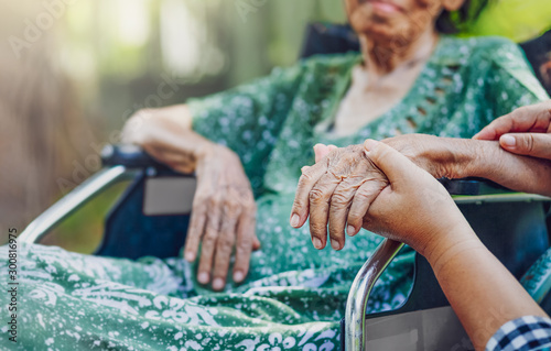 Obraz Elderly asian woman on wheelchair at home with daughter take care - fototapety do salonu