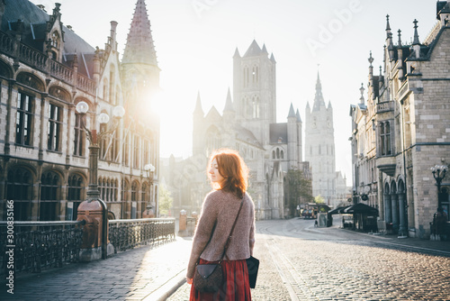 Obraz Girl walking on the city centre at the sunrise, enjoying the sights alone. Woman in backlight. Ghent, Belgium - fototapety do salonu