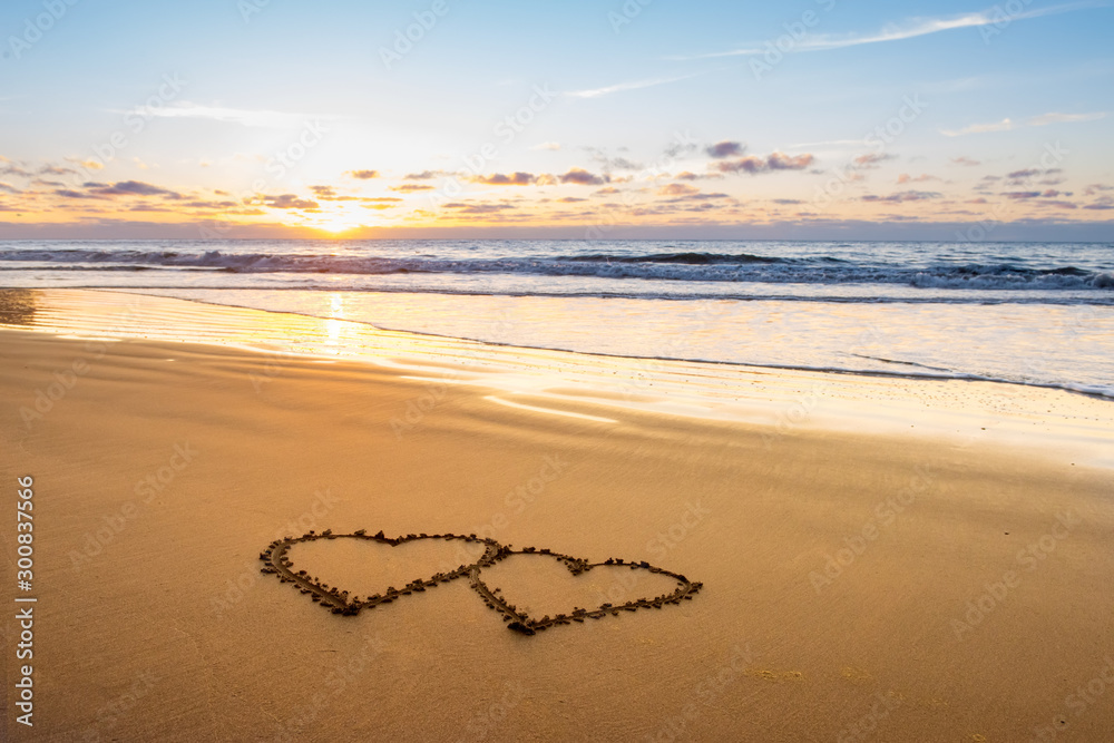 Fototapety, obrazy: Valentines day on sunny beach. Two hearts drawn in sand, love concept