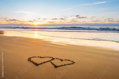 Obraz Valentines day on sunny beach. Two hearts drawn in sand, love concept - fototapety do salonu