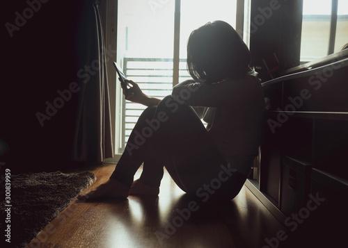 Cuadros en Lienzo Asian woman sitting on wood floor beside window light in a dark room