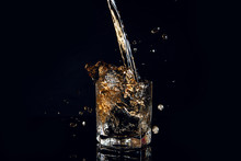 Whiskey Pouring Into Glass With Ice Isolated On Black Background..