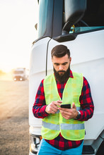 Young Handsome Bearded Man Standing In Font Of His Truck And Using Phone.