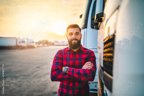 Fotomural  Young bearded man standing in front of his truck.